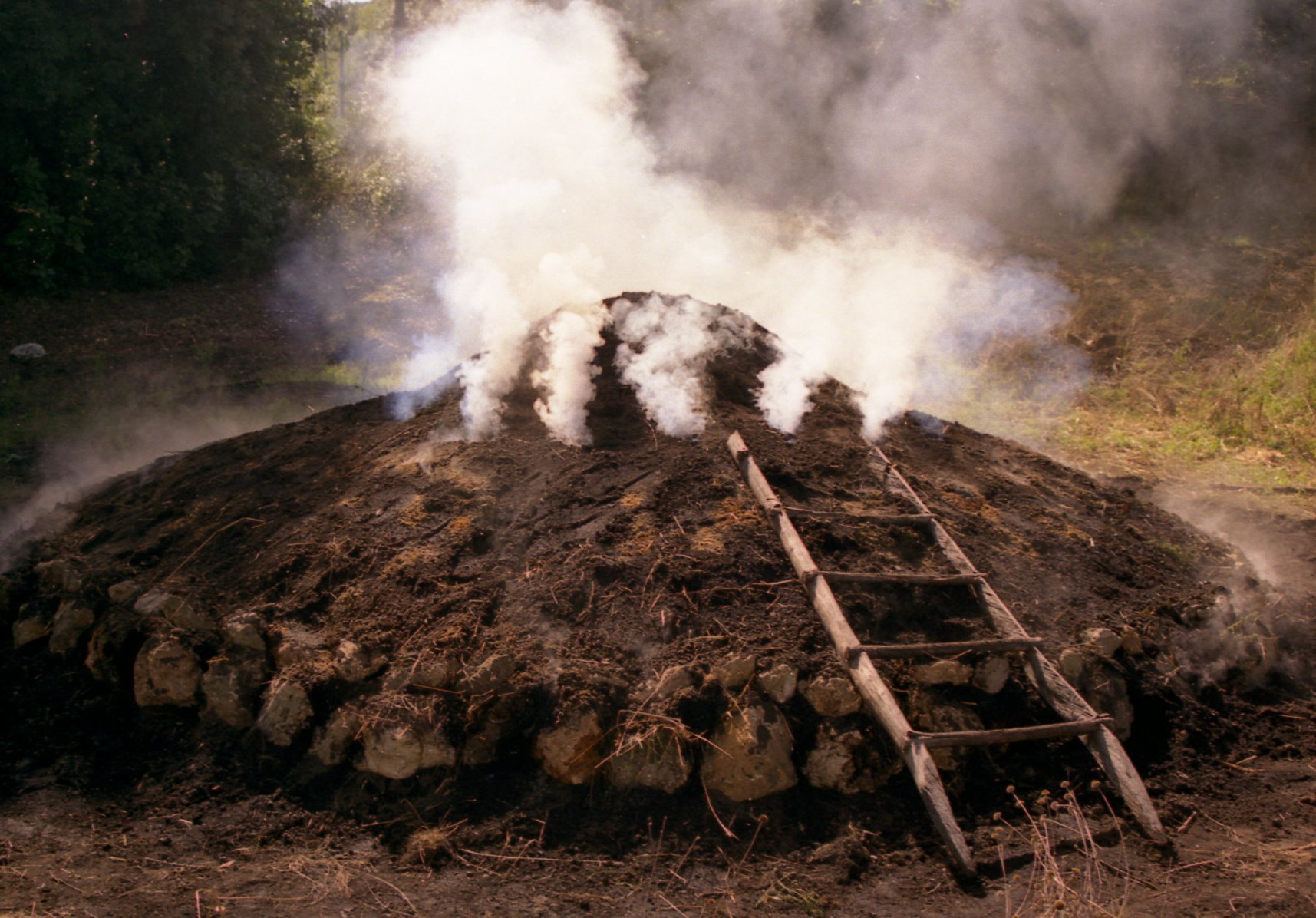 Dal primo cerchio di fori praticato alla sommità della carbonaia comincia ad uscire il fumo