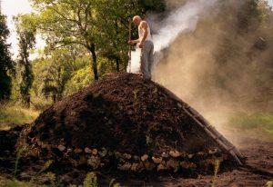 Il carbonaio si assicura che la brace e la legna introdotte nel camino arrivino fino in fondo
